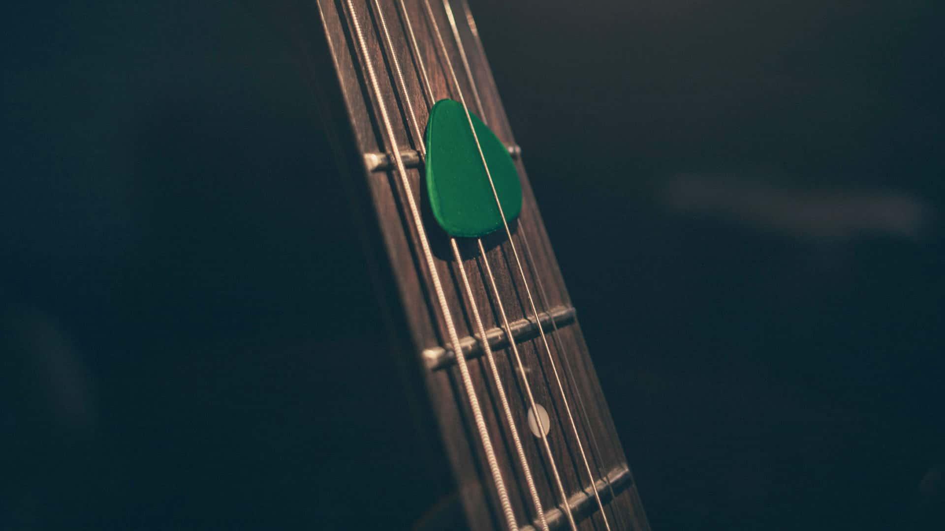 Médiator vert sur manche de guitare