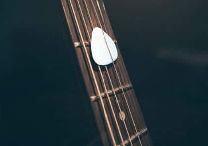 Médiator blanc sur manche de guitare